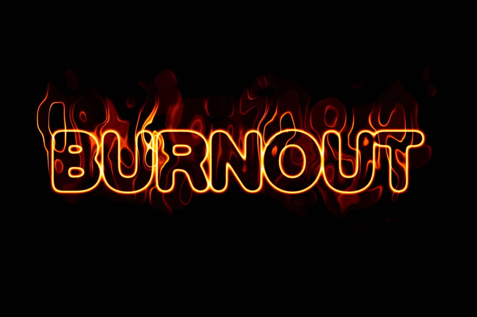 Black background with the word Burnout in neon letters and flames. This is to signify that Burnout and Imposter Syndrome are often linked.